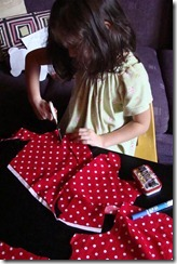 cutting out red polka dot fabric