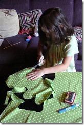 cutting out green polka dot fabric